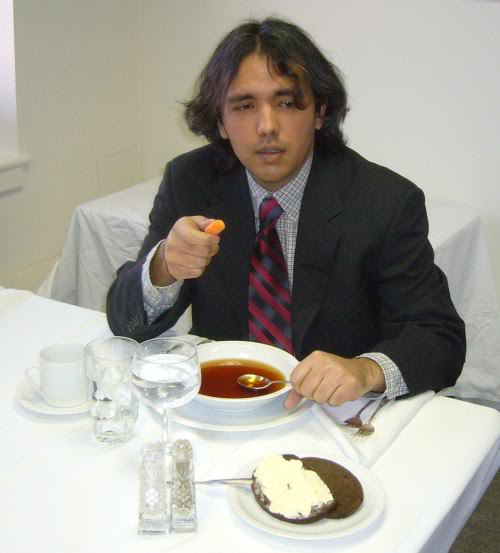 Caution: this is a professional actor. Do NOT attempt this at a business meal! There are at least eight things in this picture that demonstrate bad business etiquette. Scroll down for the answers.